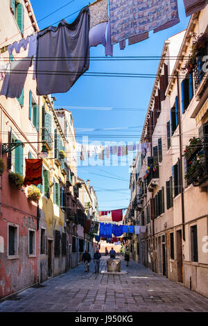 Venice,Castello. Narrow picturesque street with weathered houses,old water well, washing lines,laundry day and people walking