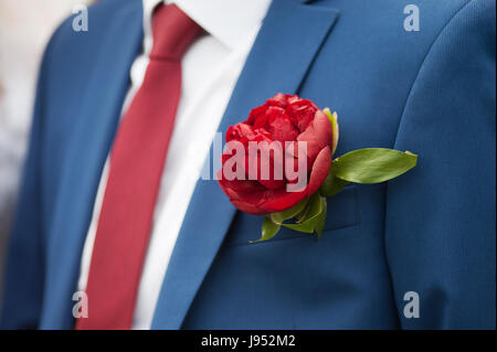 Simple wedding boutonniere on a grey suit, shot outdoors with slight filter effect. - Stock Photo