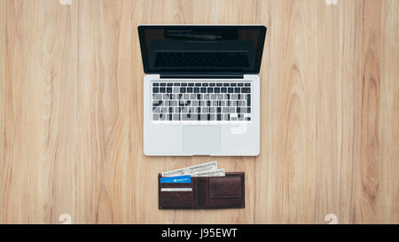 Laptop and wallet with credit card and cash money on a wooden desktop, online payment systems and banking concept - Stock Photo
