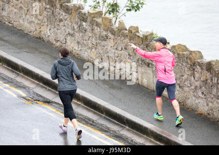 Two women jogging with one pointing as they jog along the coastal road around the great Orme at Llandudno on a wet - Stock Photo