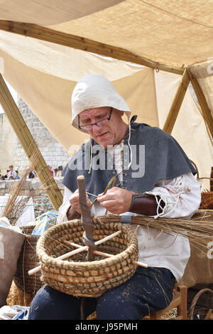 Paris, France. 4th June, 2017. A man in medieval costumes makes grass basket during a medieval festival in Dourdan, - Stock Photo