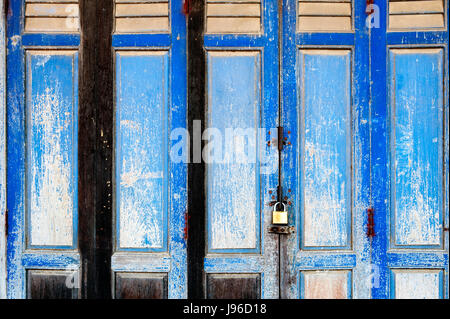 Background texture on old rustic blue wooden folding door of classic Sino-Portuguese architectural style shophouse - Stock Photo