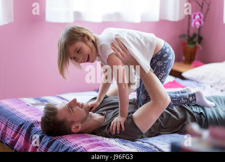 Brother and sister playing in bed - Stock Photo
