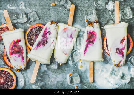 Red orange, yogurt, granola popsicles on ice cubes, concrete background - Stock Photo