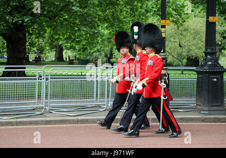 Three members of the Household Division walk down Horse Guards Parade in London following rehearsals for Trooping - Stock Photo