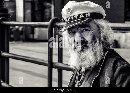 Old man with a thick beard and a captain's cap observing ships on the quay in Gdansk, Danzig - an old polish and - Stock Photo