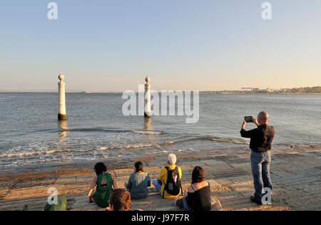 Taking a photograph in front of the Tagus river. Cais das Colunas. Lisbon, Portugal - Stock Photo