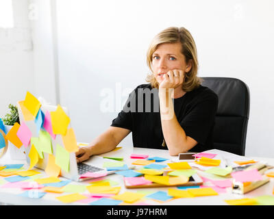 Portrait of Mature woman at office overwhelmed by adhesive notes - Stock Photo