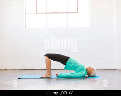 Senior woman practicing yoga on mat - Stock Photo