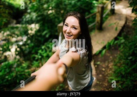 Caribbean Islands, Saint Lucia, Smiling women standing on path, holding person's hand and looking at camera - Stock Photo