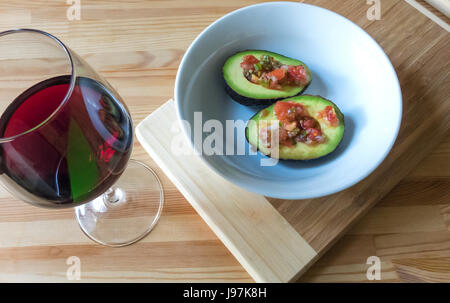 An avocado and salsa fresca in a white bowl with a glass of red wine - Stock Photo
