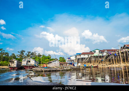Wooden houses on stilts along the river bank within Lake Sentarum in the Heart Of Borneo, West Kalimantan Indonesia. - Stock Photo