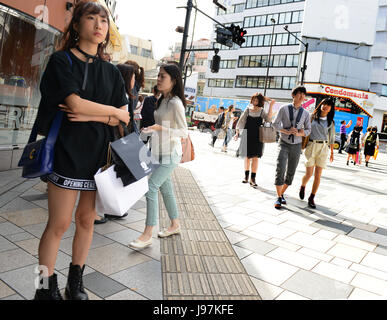 Pedestrians crossing the fashionable Omotesando street in central Tokyo - Stock Photo