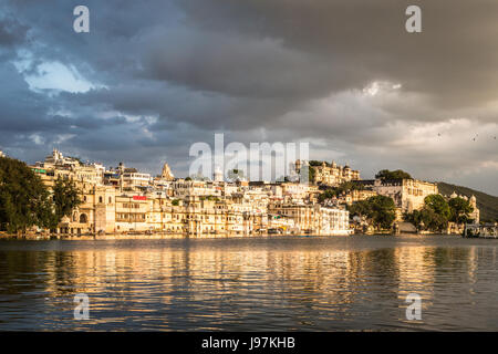 Sunset over lake Pichola with Udaipur old town lakefront and the City Palace in Rajasthan, India - Stock Photo