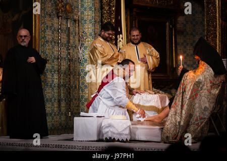 Armenian Patriarch of Jerusalem, Nourhan Manougian, washes the feet of fellow clergy during a special Maundy Thursday - Stock Photo