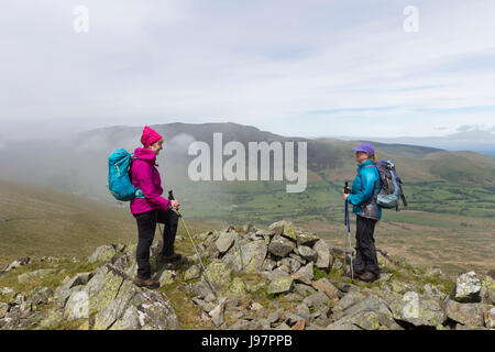 Chatting on White Pike with the Mountain of Blencathra Being Enveloped in Mist, Lake District, Cumbria, UK. - Stock Photo