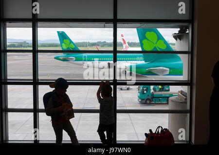 Dublin Airport, Ireland. Children watch aircraft from a terminal one window. - Stock Photo