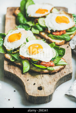 Bread toasts with fried eggs and fresh vegetables on board - Stock Photo