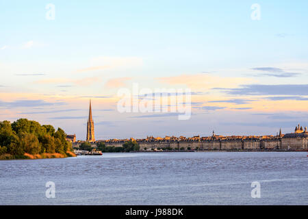 Panoramic evening view, Bordeaux waterfront and spire of St Michael's Basilica by the Garonne River, in the wine - Stock Photo