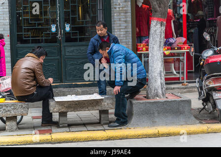 Men playing draughts in the street, Culture Street, known  for local arts and arts supplier shops, Xian, Shaanxi - Stock Photo