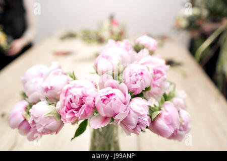 vase of peonies in the foreground. soft focus. Workshop florist, making bouquets and flower arrangements. Woman - Stock Photo