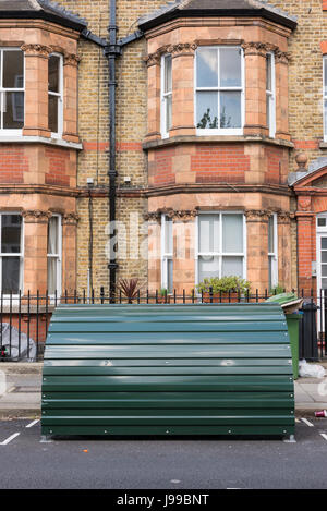 Green metal bike shed in front of a Victorian house on a street in London, UK. - Stock Photo