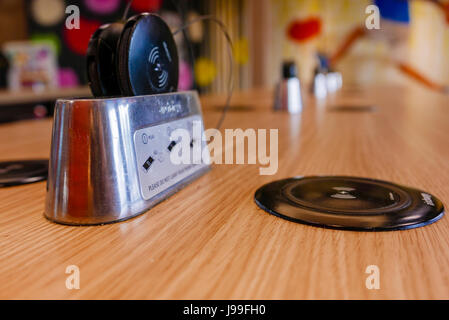 QI wireless chargers built into a table at a McDonald's restaurant, with wireless receiver adapters for devices - Stock Photo