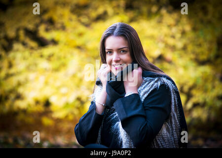 Young lady enjoying warm autumn colours in the woodlands surrounded by Canadian maple leave trees and Japanese acer - Stock Photo