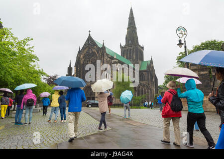 Glasgow, Scotland, UK. 1st June 2017. UK weather - colourful umbrellas outside Glasgow Cathedral on a grey showery - Stock Photo