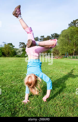 Six or seven year old girl in a blue top and pink jeans captured mid-leap while doing handstands and cartwheels - Stock Photo