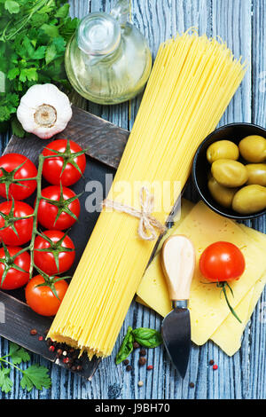 raw pasta and fresh tomato on a table - Stock Photo