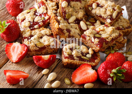 Energy food: Oatmeal bars with strawberry, pumpkin seeds and peanuts close-up on the table. horizontal - Stock Photo