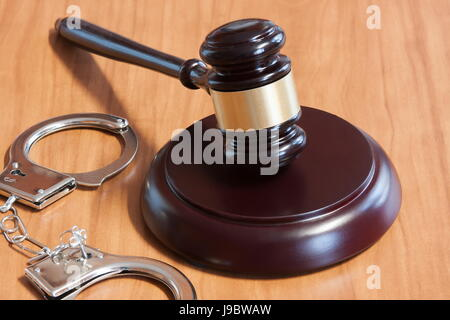 Judicial hammer and handcuffs on a wooden table - Stock Photo