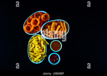 set of snacks with various dips, crispy snacks in bowls, good food, black background - Stock Photo