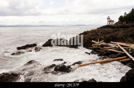 Waves crash up onto the rocks from the Pacific Ocean at this coastal lighthouse - Stock Photo
