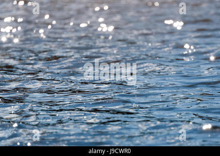 Water with bokeh background. Water surface with waves glittering in the sun - Stock Photo