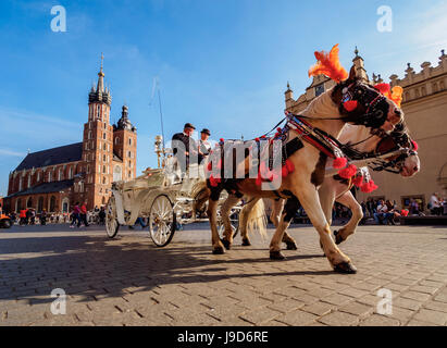 Horse Carriage with St. Mary Basilica in the background, Main Market Square, Cracow, Lesser Poland Voivodeship, - Stock Photo