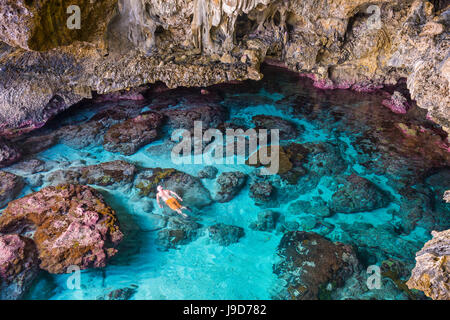 Tourists swimming in the amazing Avaiki rock tide pools Niue, South Pacific, Pacific - Stock Photo