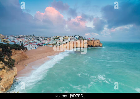 View of Carvoeiro village surrounded by sandy beach and turquoise sea at sunset, Lagoa Municipality, Algarve, Portugal, - Stock Photo