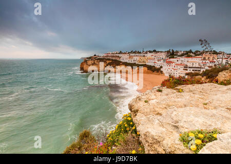 Clouds on Carvoeiro village surrounded by sandy beach and turquoise sea, Lagoa Municipality, Algarve, Portugal, - Stock Photo