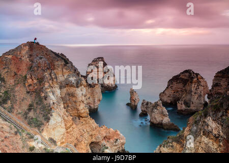 Photographer on top of cliffs surrounded by sea under the pink sky at sunrise, Ponta Da Piedade, Lagos, Algarve, - Stock Photo