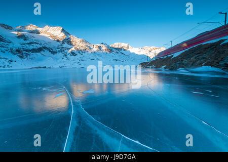 The Bernina Express train runs beside the frozen Lago Bianco, Bernina Pass, canton of Graubunden, Engadine, Switzerland, - Stock Photo