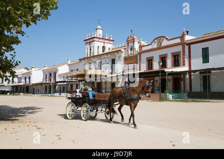 Horse and carriage riding along sand streets with brotherhood houses behind, El Rocio, Huelva Province, Andalucia, Spain, Europe