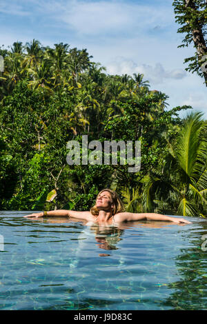 Woman enjoying an overflowing pool above a valley in the Kamandalu Ubud resort, Ubud, Bali, Indonesia, Southeast - Stock Photo
