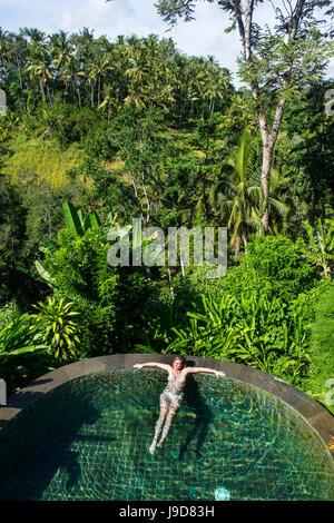 Woman enjoying an overflowing pool above a valley in the Kamandalu Ubud resort, Ubud, Bali, Indonesia, Southeast - Stock Photo
