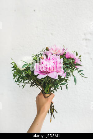Bouquet of pink and white peony flowers in woman's hand - Stock Photo