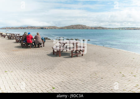 people sitting at a table with wondeful views looking from the isle of Iona looking back to the shores of Mull - Stock Photo