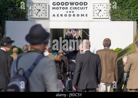 Crowd of people squeezing squashing together whilst walking through the tunnel at goodwood motor racing circuit - Stock Photo
