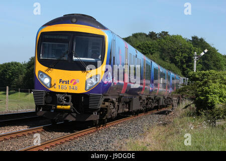 Siemens Desiro diesel multiple unit train in First Transpennine Express livery leving Arnside railway station past - Stock Photo