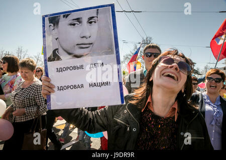 A woman holds a portrait of young Vladimir Putin with the inscription 'Healthy children - healthy nation!' on the - Stock Photo